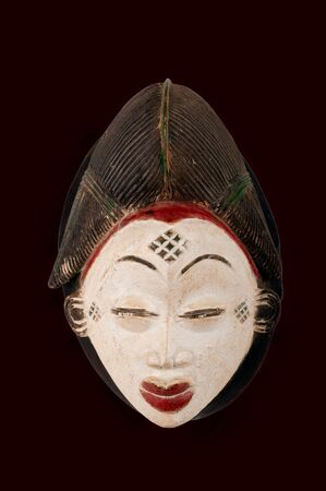 Punu female mask from Cameroon, Africa, carved in wood isolated on black
