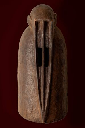 African monkey mask carved in wood isolated on black.