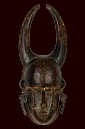 Interesting African Mask with four eyes and three noses and two horns isolated on black.