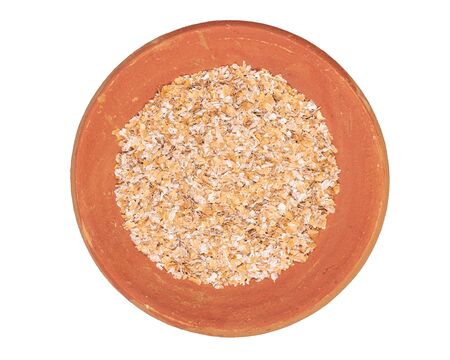 Food texture background of cracked durum wheat or cereal groats, top view in terracotta red plate.
