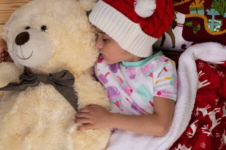 Sleeping girl at home at Christmas time with large Teddy bear plush toy. New Year winter holiday concept. 写真素材