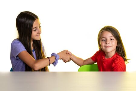 Two young girls give handshake isolated on white, concept of successful teamwork or congratulating each other.