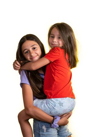 Young teen girl holding in her arms her little friend and hapilly looking at camera, isolated on a white background.