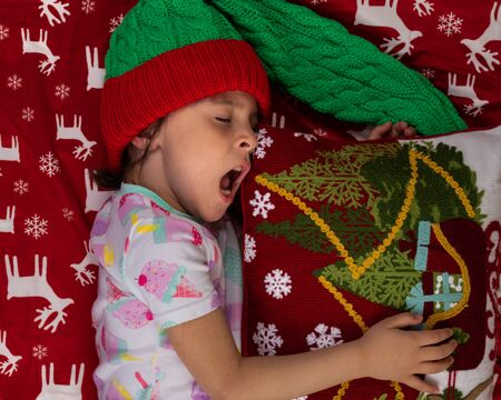 Yawning girl at home at Christmas time with large Teddy bear plush toy. New Year winter holiday concept.