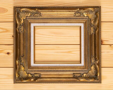 Ornate gold picture frame isolated on on a wooden background. 写真素材