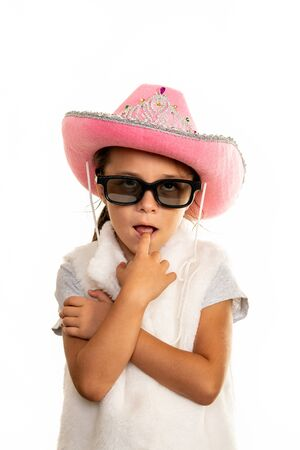 Young girl in cowboy hat and sunglasses posing on a white background.