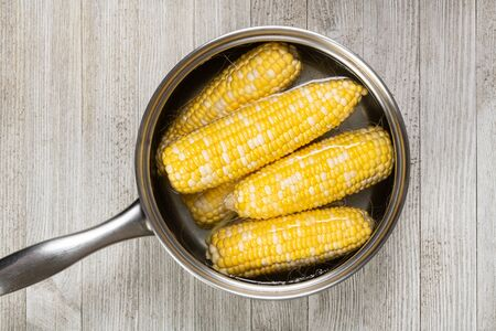 Ready to be boiled farm fresh yellow corn in water in a stainless steel pot isolated on a wooden table.