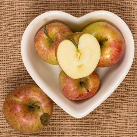 Organic fresh farm honey crisp apples photographed from above in a heart shaped bowl.