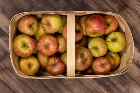 Organic fresh farm honey crisp apples photographed from above in a basket on a wooden table. 写真素材
