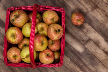 Organic fresh farm honey crisp apples photographed from above in a red wicker basket on a wooden table. Copy space.