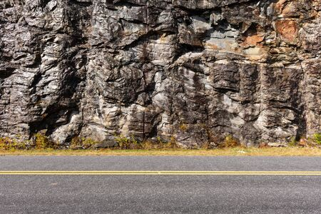 Wet mountain side rocky background after recent rain behind divided highway. 写真素材