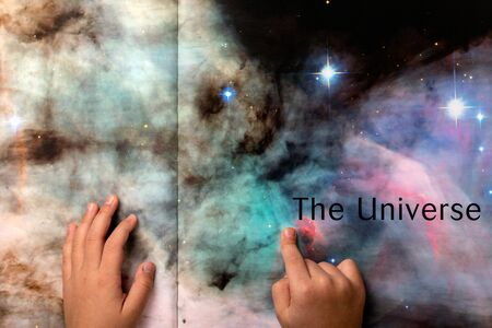 Child with hands visible looking at book pages depicting the vast universe. Infinite power of imagination concept. 写真素材