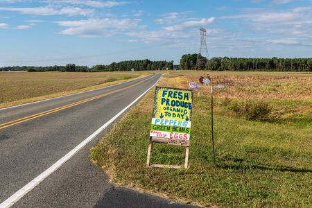 A handmade sign advertising farm products on the side of a country road. Stock fotó