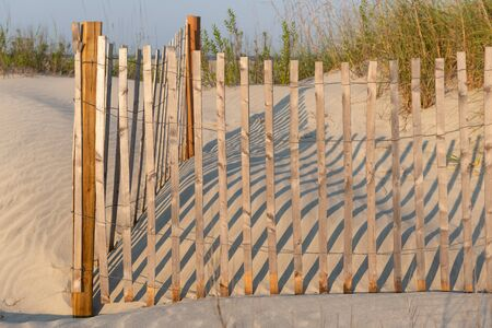A typical wooden fence along the barrier sand dunes designed to keep tourists and children away from protected sandy areas.