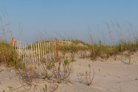 A typical wooden fence along the barrier sand dunes designed to keep tourists and children away from protected sandy areas. Stockfoto