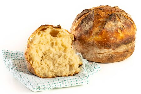 A homemade baked loaf of round artisan white sourdough bread isolated on white.