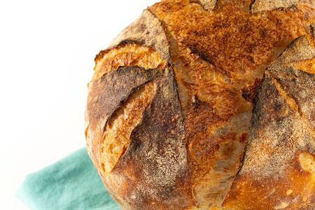 Macro shot of a homemade baked loaf of artisan white sourdough bread isolated on white.