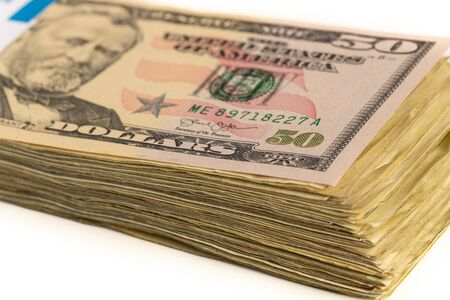 Stack of American dollars with a $50 bill on top isolated on a white background. 版權商用圖片