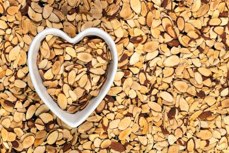 Roasted pile of sliced almonds in a heart-shaped bowl. 스톡 콘텐츠