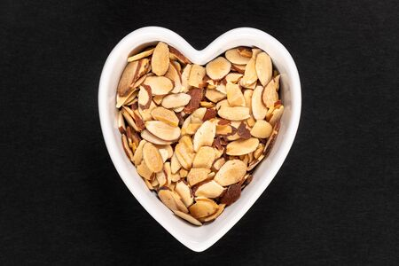 Roasted pile of sliced almonds in a heart-shaped bowl isolated on a back background.