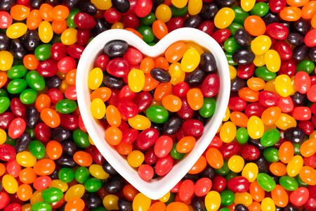 Assorted colourful black, red, green, yellow, and orange jelly beans, sweet candy background with a heart shaped bowl. Kids junk food.