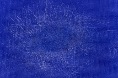 Blue, plastic, grained cutting board with a lot of scratches.