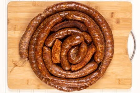 Smoked homemade stuffed pork sausages and bacon isolated on a woodboard. Stok Fotoğraf