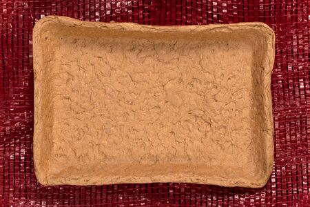 Recycled brown cardboard food container isolated on a red woven plastic net.