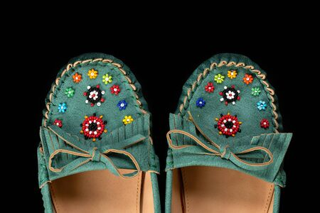 Fragment of women summer shoes decorated with multicoloured beads.