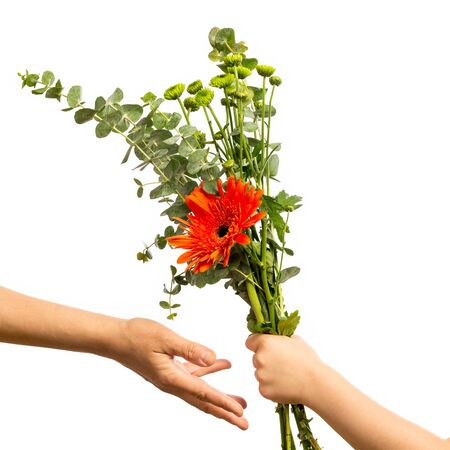 Child hand holding a bouquet of flowers isolated on a white background. Mothers Day Concept.