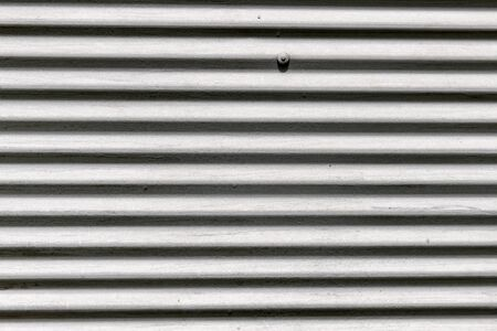 Old white corrugated metal wall with bolts, frontal background texture. 스톡 콘텐츠