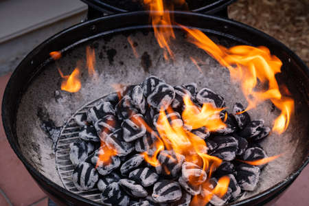 Close-up of blazing fire in rustic BBQ grill at evening. Stock Photo
