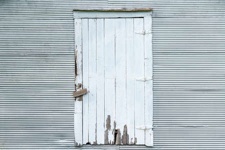 Old wooden door on white corrugated metal wall with bolts, frontal background texture.