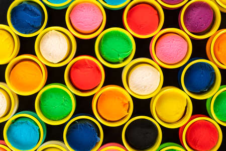 Abstract background from colorful containers of pastel colored playdough on black background. Graphic, artistic. Imagens
