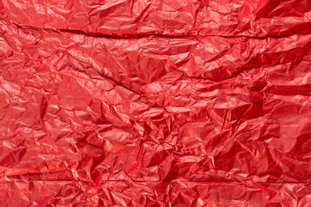 Bright red wrapping paper, crumpled paper texture. Creased sheet background. Textured effect.