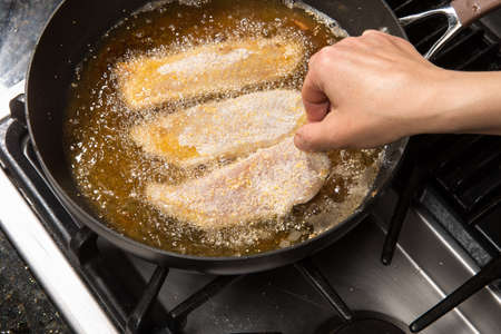 Pan-frying or home cooking fish fillet on a stove top.