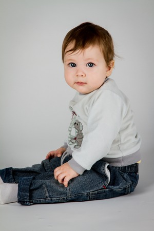 Little boy sits on a white background