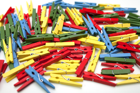 Multi-coloured clothespins on a white background