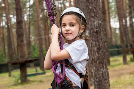 Girl climber hanging on insurance in the forest Stock Photo