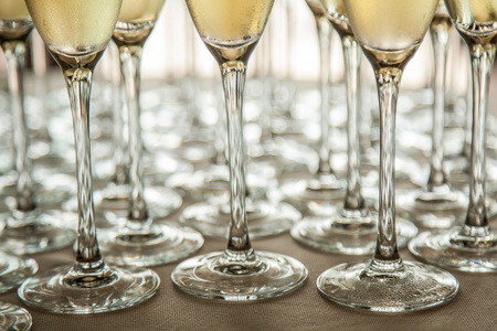 Legs of glasses with cold champagne, close-ups Stock Photo