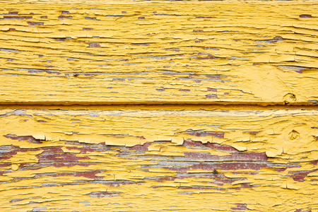 Old shabby yellow paint on the board