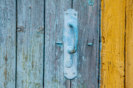 Old blue door handle made of metal on a wooden door