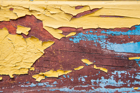 Old peeling paint on the board. Blue and orange background.