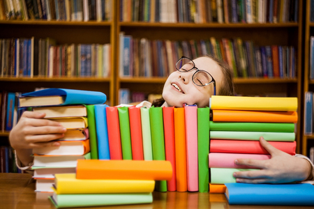 The girl in glasses in the library hugs books. Stock Photo