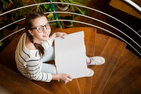 Girl in glasses with a book in her hands sitting on the stairs