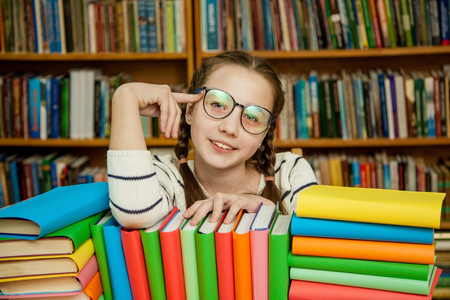 Happy girl in glasses with books in the library.