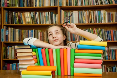 Girl dreams with books in the library Stock Photo