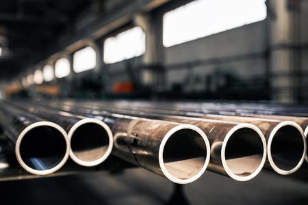 Metallische Rohre im Lager, Reihen von Metallrohren im Industrielager. Industrielles Interieur,