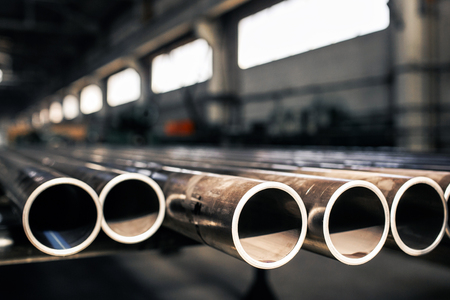 Rury metalowe na magazynie, rzędy rur metalowych na magazynie przemysłowym. Wnętrze przemysłowe,