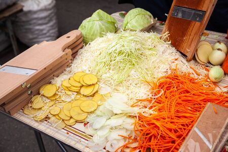 Chopped carrot and cabbage on a wooden cutting board. Assortment of fresh vegetables. Healthy food conception. Top view, rustic style, horizontal